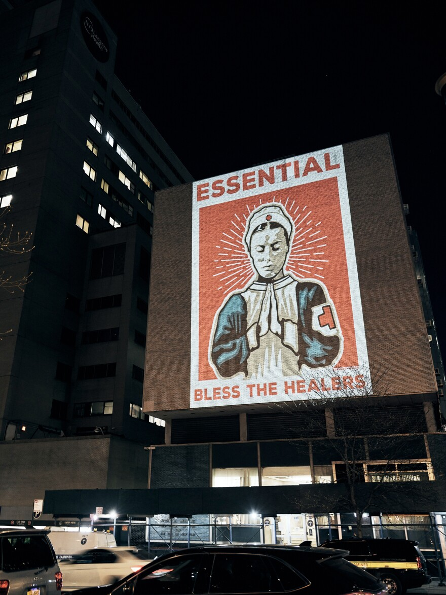 """Essential,"" a poster design by Marvin Madariaga, is projected onto a hospital building in New York City. It was submitted to the arts group Amplifier's open call for pandemic art."