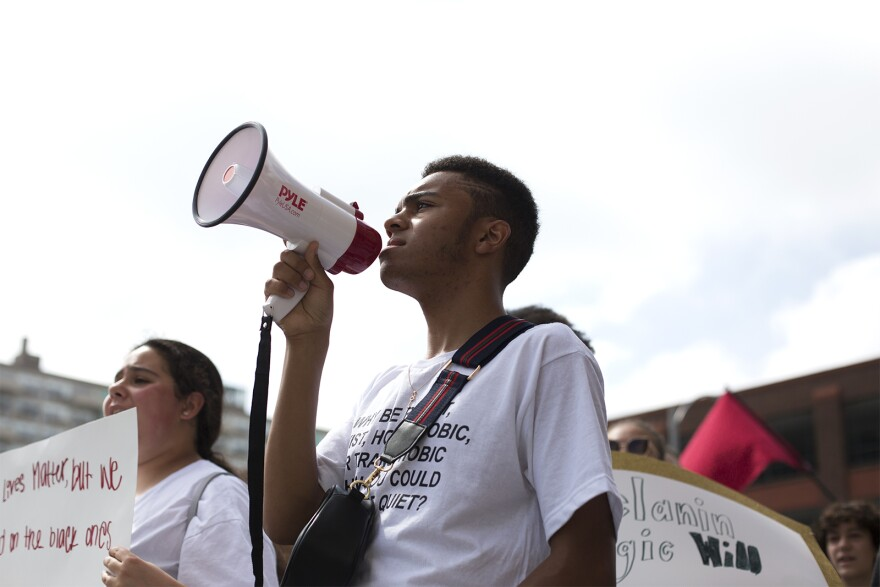 Co-organizer Devin Corley leads a chant while marching down Olive Street. (May 19, 2018)