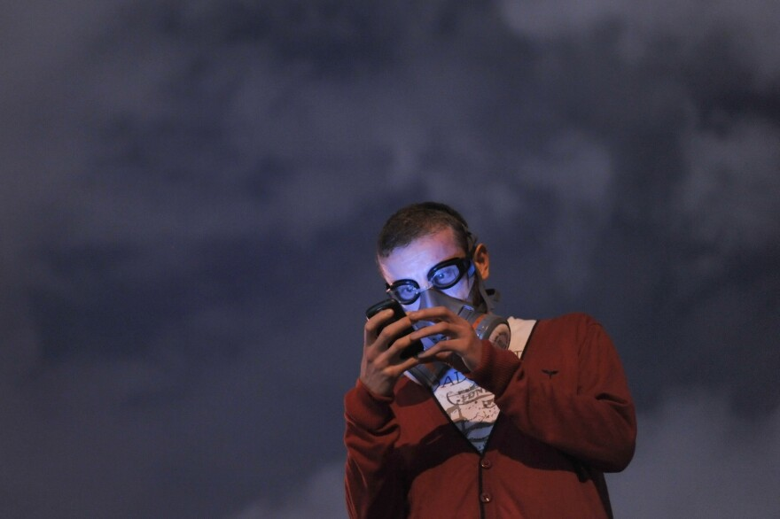 A protestor with a gas mask uses a mobile phone to read the news on social media as demonstrators gather at midnight Thursday in Istanbul's Taksim Gezi Park.