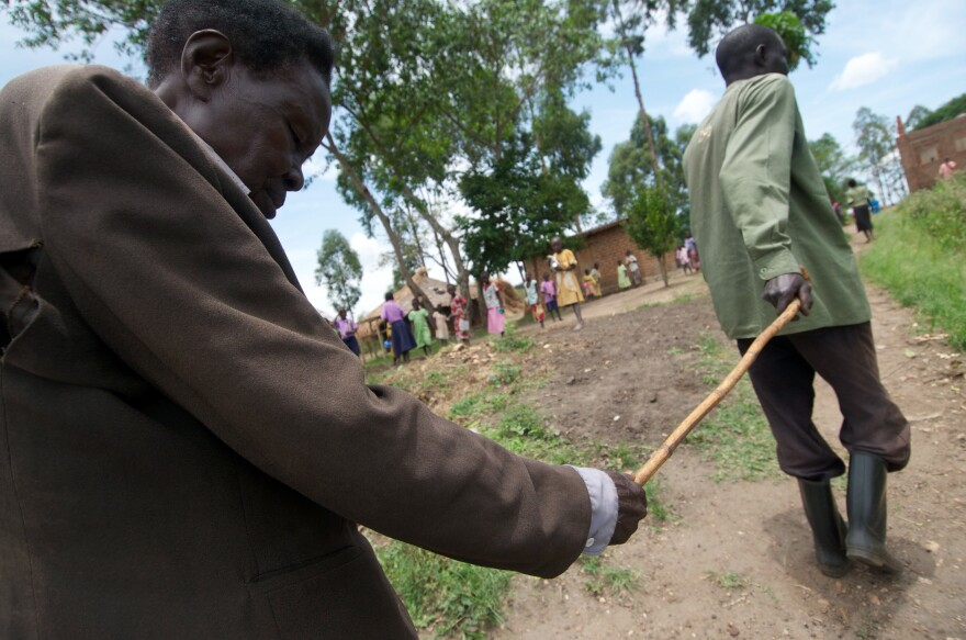 Oromdi Yallo Lambert leads his blind father, Fabiano Olur, who lost his sight to river blindness, in Nebbi district, Uganda.