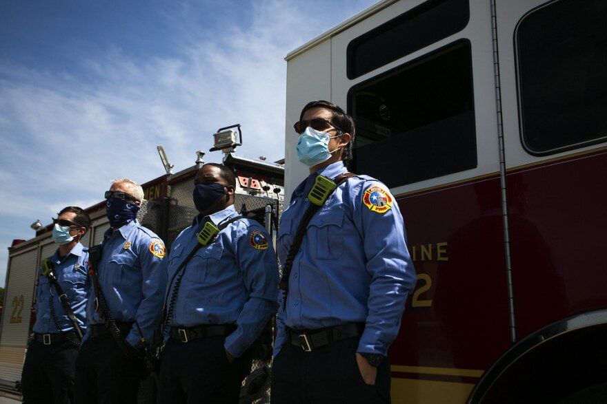 Firefighters don face masks April 20 as they await a procession for a San Marcos police officer who was killed responding to a domestic violence call. The procession was rerouted.