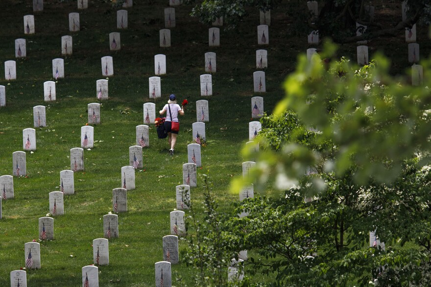A volunteer places flowers at the base of tombstones during an event at Arlington National Cemetery in in Arlington, Va., ahead of Memorial Day. (Tom Brenner/Getty Images)