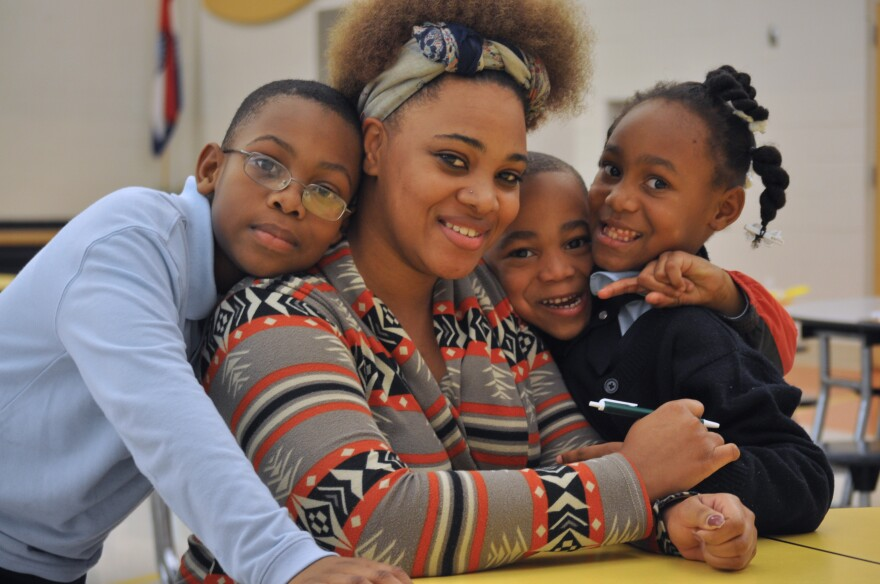 Carnadria Smith sits with her three children after a public input session for parents at Lucas Crossing Elementary School in Normandy.