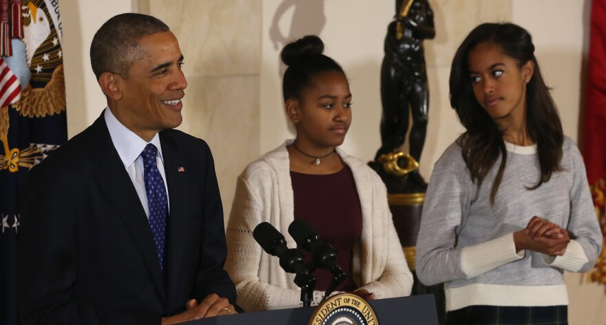 """President Obama's daughters, Sasha, middle, and Malia, right, look on as their father speaks, and jokes, before pardoning """"Cheese"""" and his alternate """"Mac"""" in 2014 at the White House turkey pardoning."""