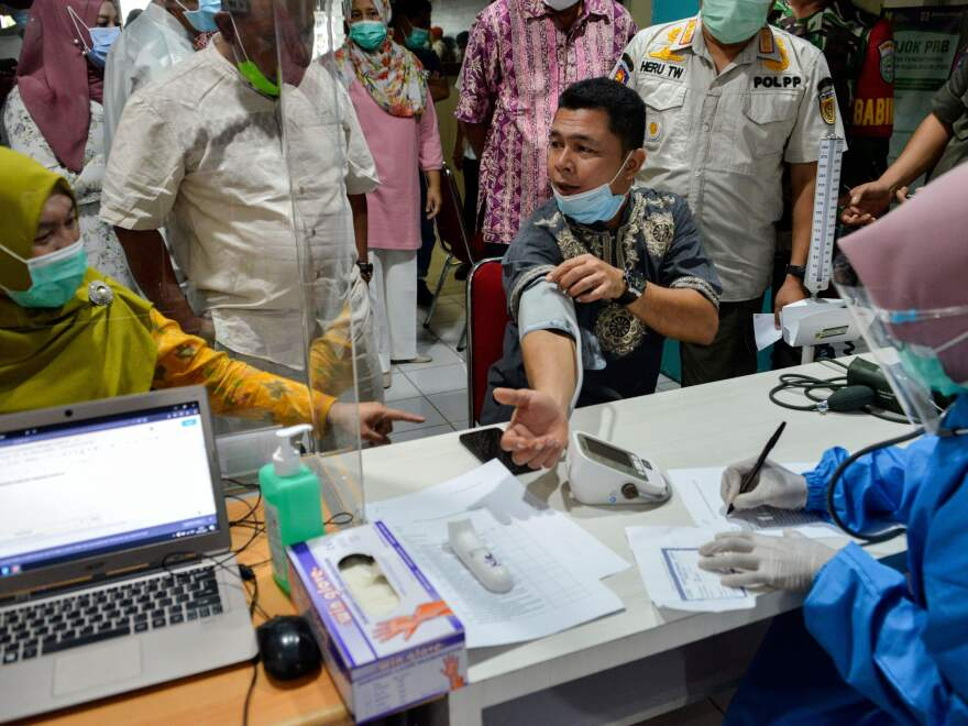 An official has a blood pressure test before receiving the Sinovac vaccine against the Covid-19 coronavirus at Meuraxa Hospital in Banda Aceh on January 15, 2021.