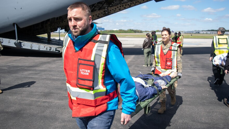 Two men carry a mannequin on a stretcher off a cargo airplane
