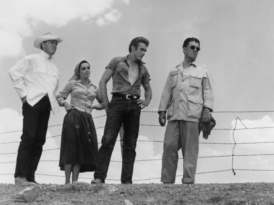 <em>Giant</em> was based on the 1952 novel by Edna Ferber. Above, (left to right) George Stevens Jr., Elizabeth Taylor, James Dean and director George Stephens appear on location in Texas.<em></em>