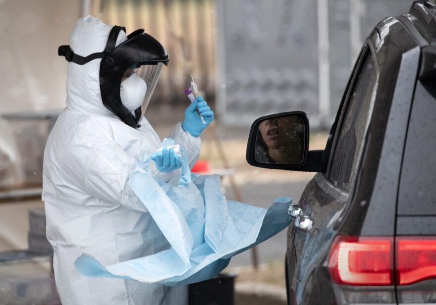 A nurse dressed in personal protective equipment prepares to give a coronavirus swab test at a drive-thru testing station in Stamford, Connecticut.