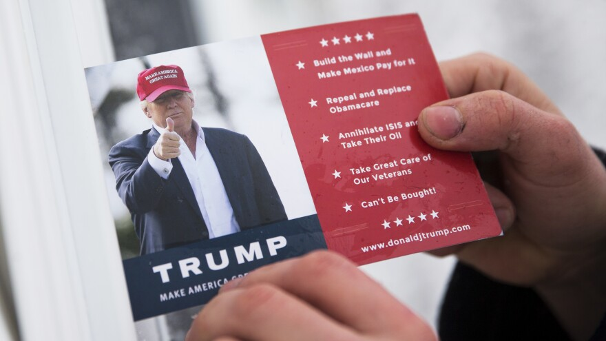 A volunteer for Republican presidential candidate Donald Trump leaves a card in a front door as he canvasses a neighborhood in New Hampshire.