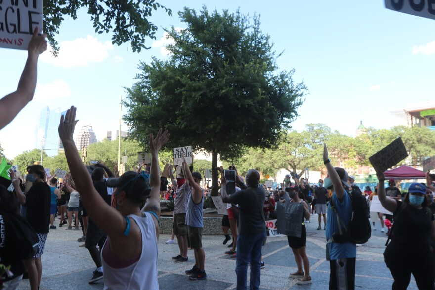 "Protesters stand with their hands up, saying ""Don't shoot,"" in honor of the Black lives lost at the hands of the police."