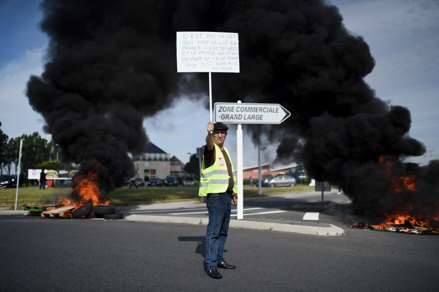 A protester holds a banner as people gather Thursday in Saint-Nazaire, in western France, to demonstrate against the government's proposed changes to labor law.