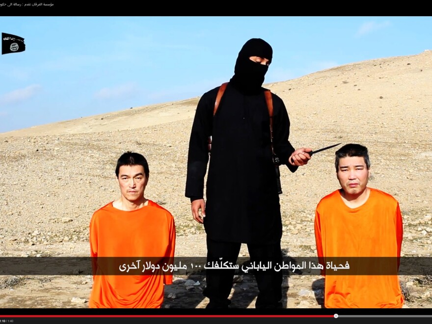 A central figure in videos released by the self-declared Islamic State has been identified as a man from West London. He's seen here dressed in black, threatening Japanese captives Haruna Yukawa (right) and Kenji Goto.