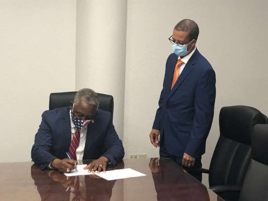 Orange County Mayor Jerry Demings signs and executive order mandating the wearing of face masks in public.