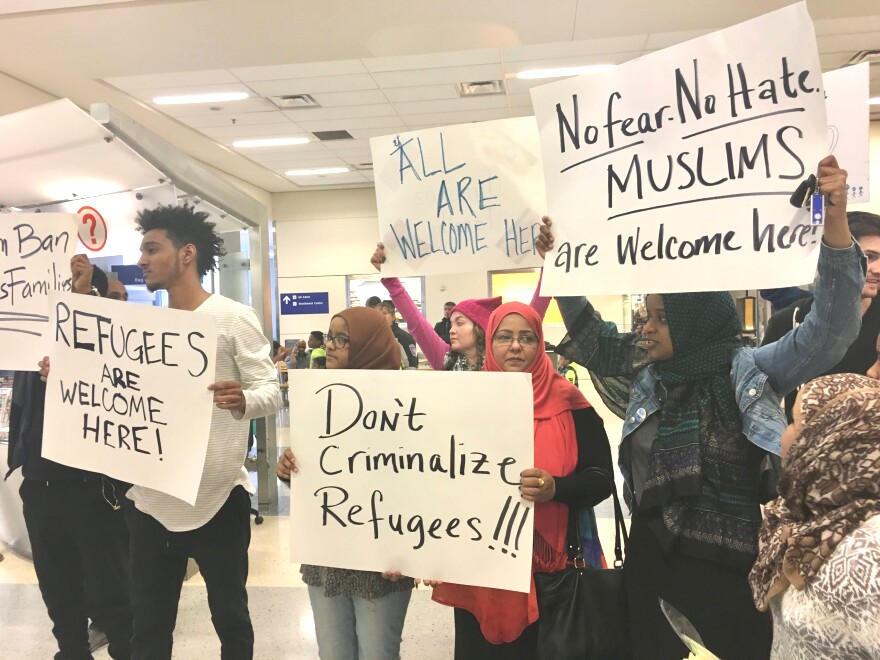 "Protesters hold signs that say ""Refugees are welcome here!"" and ""No fear, No Hate, Muslims are welcome here"" inside Dallas-Fort Worth International Airport."