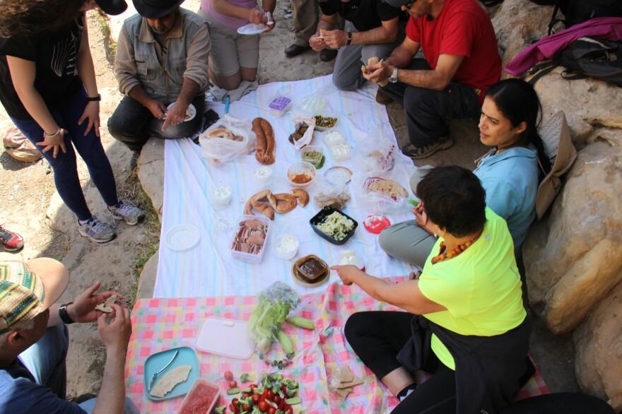 "Hikers spread tablecloths on the rocks for an al fresco meal as part of a Shat'ha (""Picnic"") group hike."