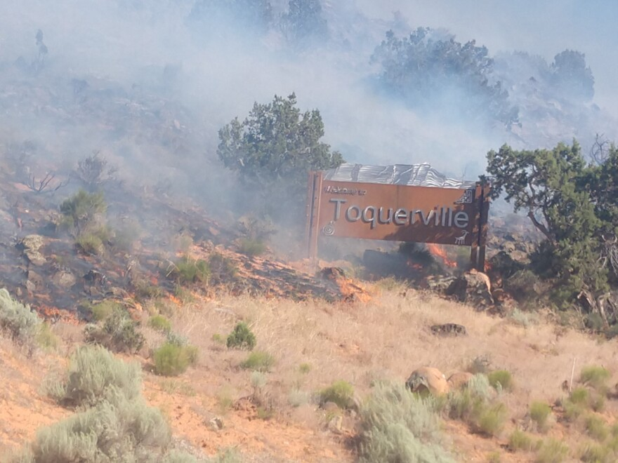 Photo of burning pinyon and juniper beside Toquerville sign.
