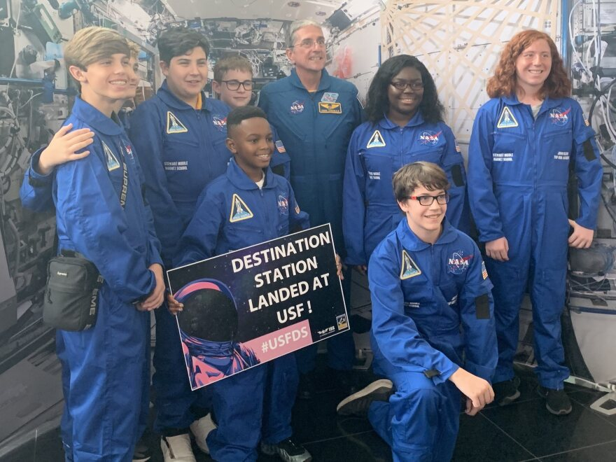Former shuttle astronaut Don Thomas poses with students from Stewart Middle School's space magnet program. All are dressed in blue astronaut uniforms.
