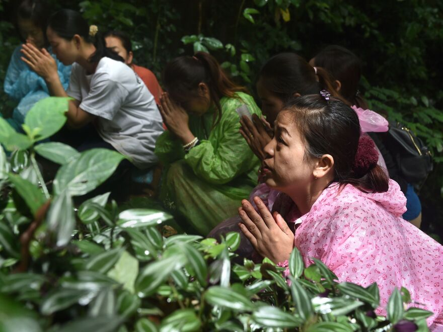 Relatives of the missing boys pray outside of the cave on Wednesday, as rescue personnel continue their frantic mission.