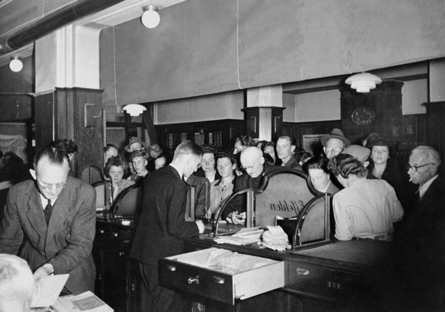 Germans wait to change their pre-World War II currency, the reichsmark, into deutschemarks, which were introduced in 1948 in western Germany. The deutschemark was later replaced by the euro.