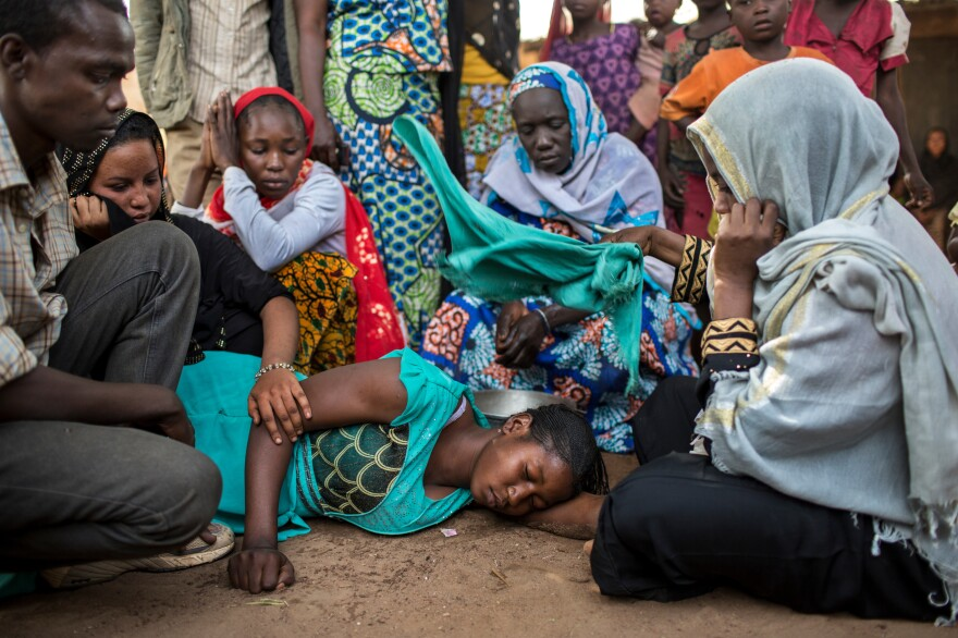 People comfort the sister of a Muslim man who was kidnapped, held for ransom and then murdered when his family could not pay the amount demanded by kidnappers in Paoua town. Kidnapping and extortion are part of the scene in lawless areas of the Central African Republic.