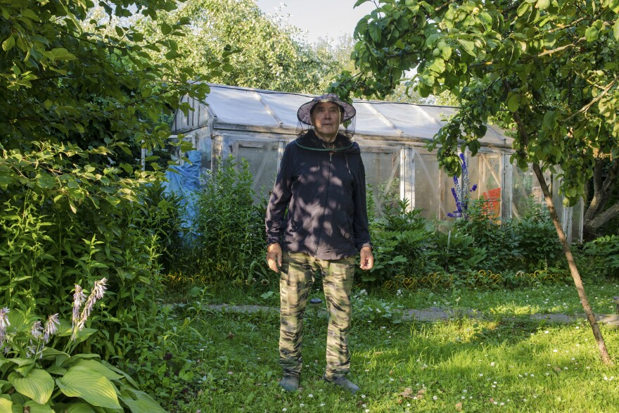 """Vladimir wears a protective net against horseflies.  He says his two sons rarely visit him. """"The dacha is not for everyone,"""" he admits."""