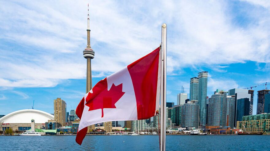Canadian flag and the Toronto skyline.