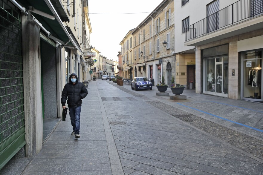 A man wearing a face mask walks along a street in Codogno, in northern Italy.