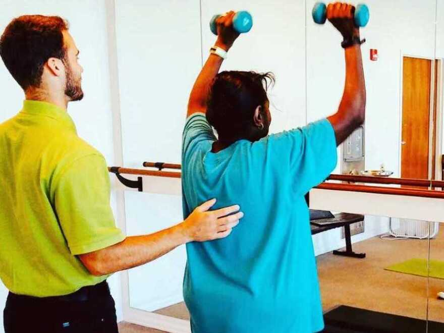 Nick Cumer guides a patient of Maple Tree Council Alliance through strength training exercises.