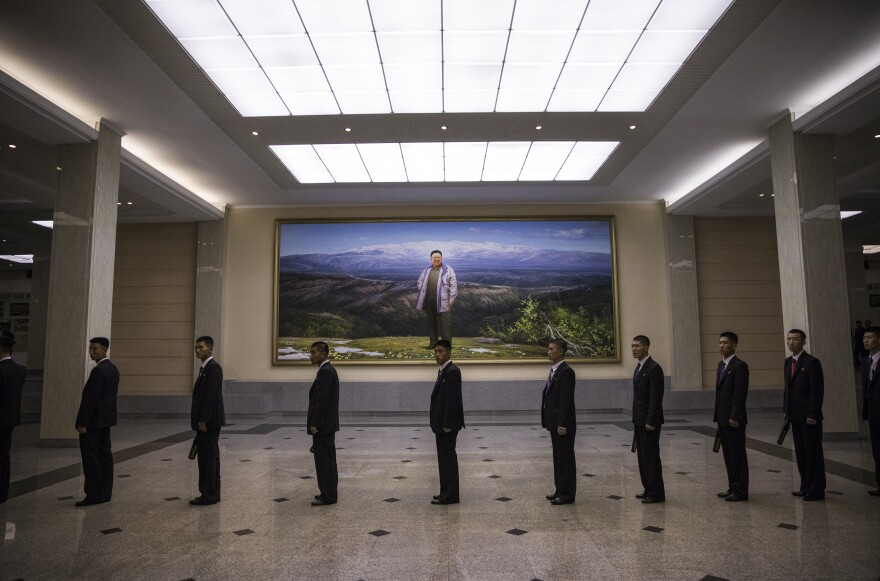 Security guards with metal detector wands line up ahead of an orchestra performance at the Mansudae People's Theater in Pyongyang. Behind them is a portrait of Kim Jong Il, North Korea's second leader, standing at the top of Mount Paektu — the spiritual home of the Korean people where, according to official North Korean mythology, Kim was born.