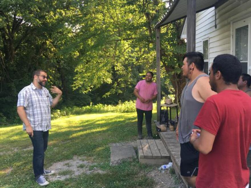 Attorney Alex Enyart (left) speaks with migrant workers in Cobden, Illinois.