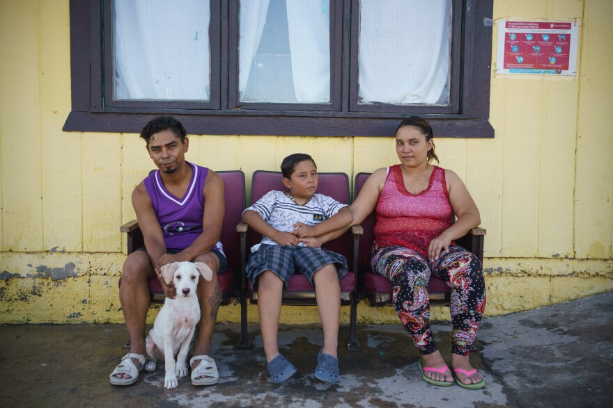 Cesar, Carolina and Donovan sit on theater style chairs with a dog in front of shelter