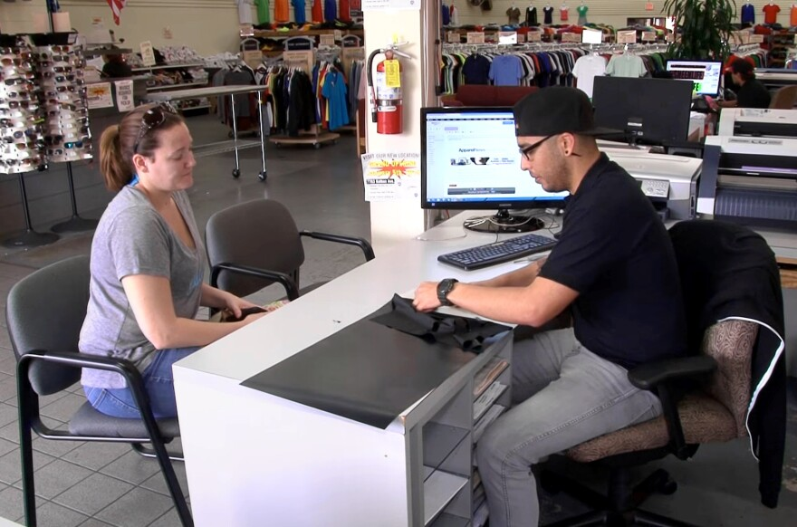 Christopher Avila, a National Guardsman, works with a customer in March during a shift at T-Shirt Mart in Point Loma, Calif. He says he lost an IT job because the guard needed him for two straight weekends, followed quickly by two weeks of training on new equipment.