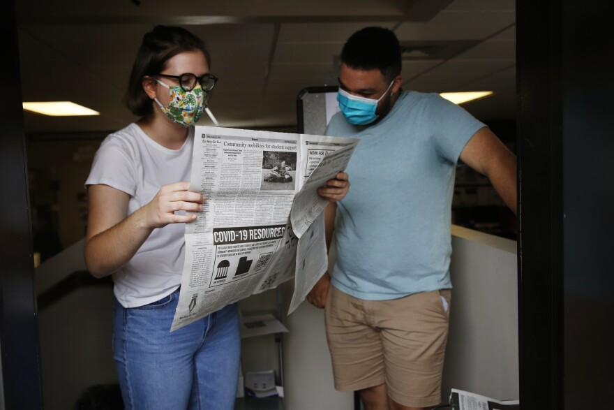 Student journalists Anna Pogarcic and Brandon Standley of UNC's <em>Daily Tar Heel</em> review a recent issue at their offices off campus.