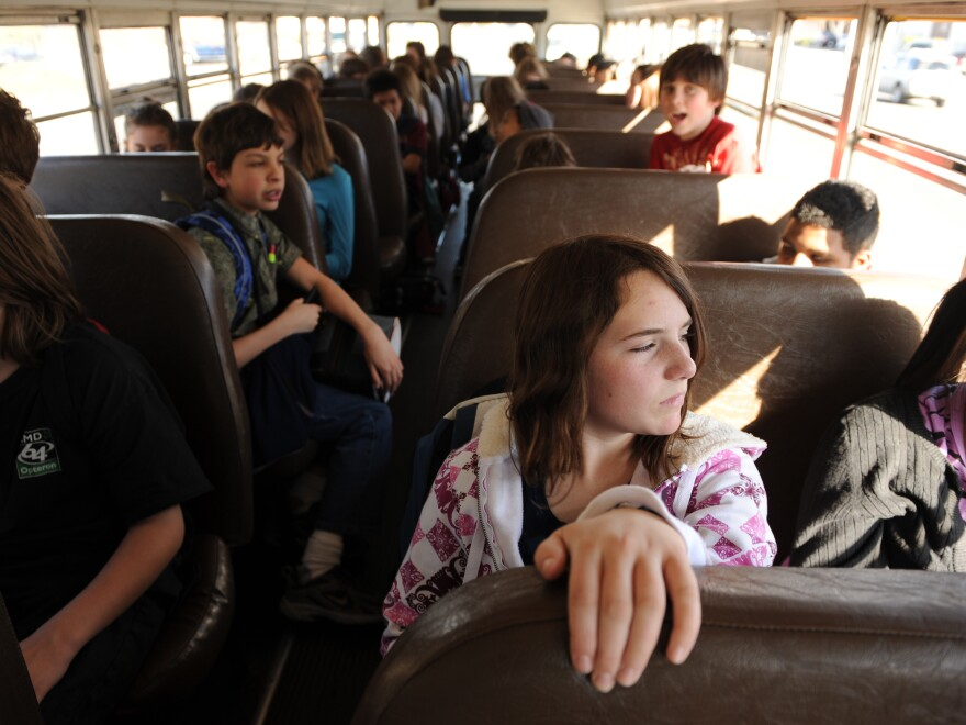 Kids slog to school on a bus.
