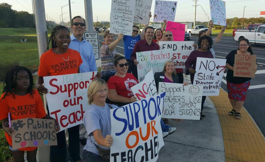 A group of parents and teachers rallied at U.S. 98 exit