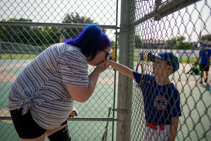 Gavin, 6, holds out his hand to his mother, Heather Stalley, from the excavated hole after finishing her first match with the Miracle League.