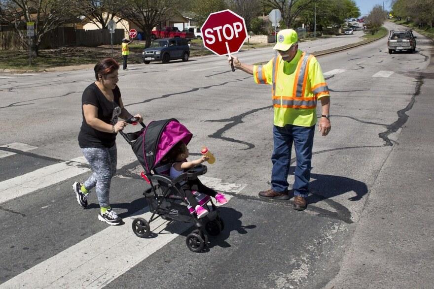 Richard Tuttle helps people cross the street near Mendez Middle School in Southeast Austin.
