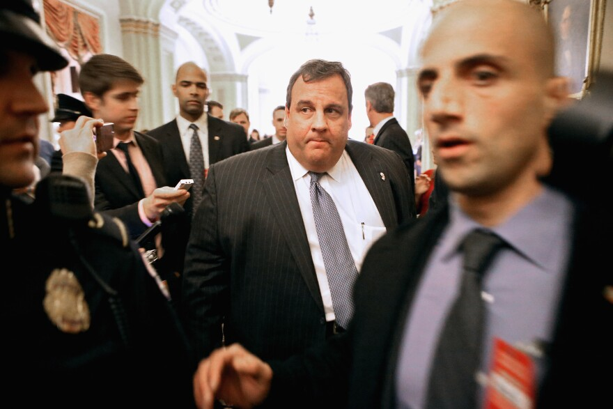 New Jersey Gov. Chris Christie is surrounded by security and journalists in 2012.