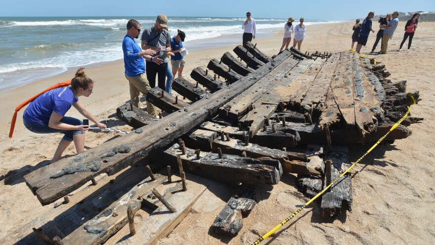 Staff from the St. Augustine Lighthouse Archaeological Maritime program examine the remains of a ship Wednesday that washed up in south Ponte Vedra.