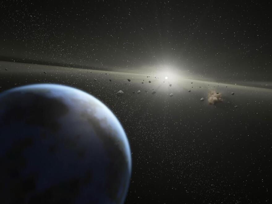 "A NASA artist's illustration depicts an asteroid belt around a star that the space agency says is ""the same age and size as our Sun."""
