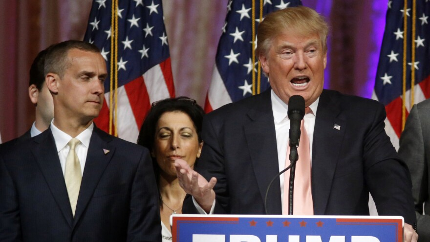 Corey Lewandowski listens (at left) as Donald Trump speaks at a campaign news conference in Palm Beach, Fla., earlier this year.