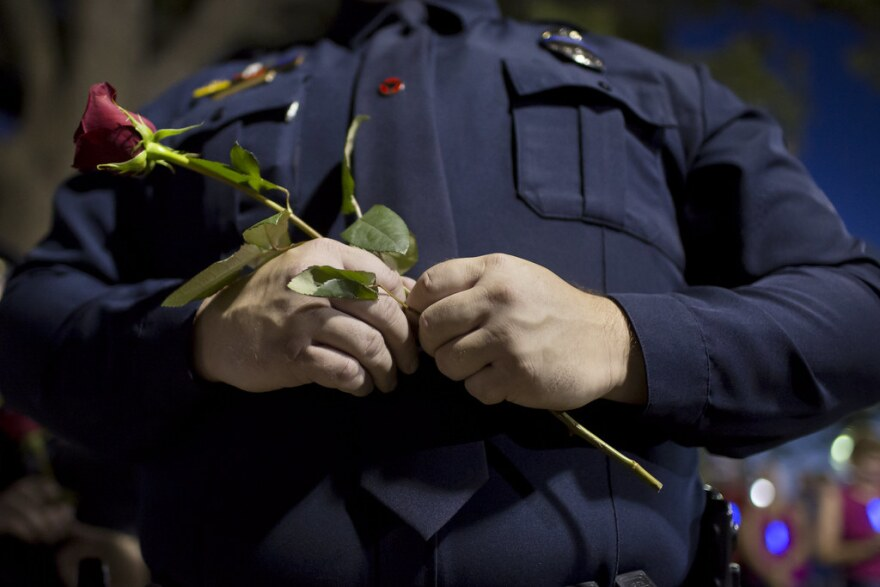 A police officer holds a rose