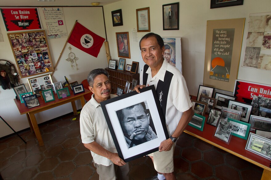"""Roger Gadiano (left) and Alex Edillor hold a photo of grape strike leader Larry Itliong, whom they respectfully refer to as """"The Man."""" Itliong convinced Filipino grape worker to go on strike in 1965, a step that set in motion the Farmworker Movement."""