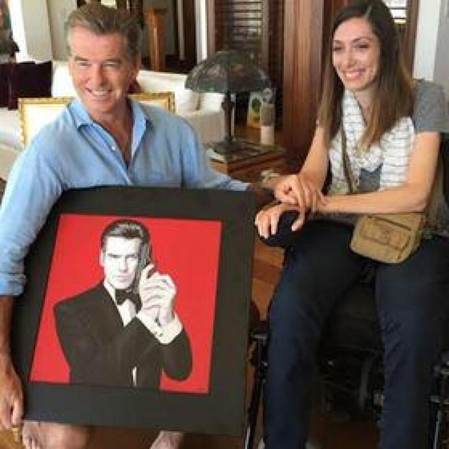 Artist Miriam Paré presents actor Pierce Brosnan with a portrait she painted with her mouth of him as Agent 007.