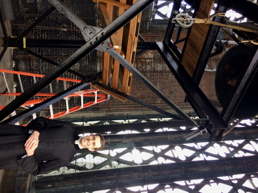 Father David Silvey stands below steel frame that houses four bronze bells in the the tower of St. Francis De Sales Oratory.