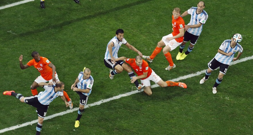 Players go for the ball during the World Cup semifinal soccer match between the Netherlands and Argentina at the Itaquerao Stadium in Sao Paulo, Brazil, on Wednesday.