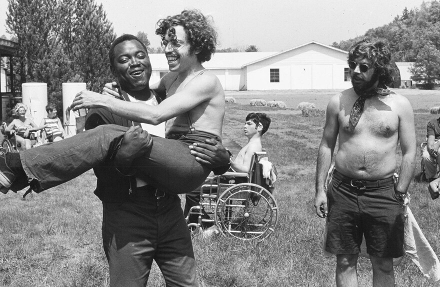 A still from the film Crip Camp showing a man smiling and holding another man, with another man standing beside him and another man in a wheelchair behind them.
