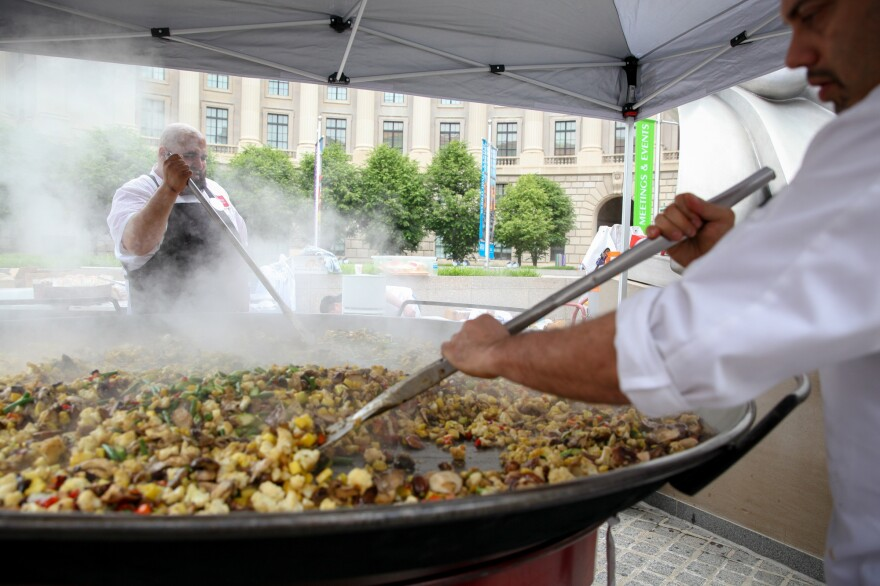 Chefs cook vegetables that will be added to a giant, 7-foot-wide platter of paella. The dish, made from produce diverted from the dump, was served up as part of a free feast for 5,000 in Washington, D.C., Wednesday to raise awareness about food waste.