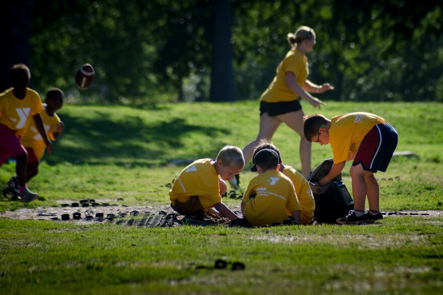 Children play in the dirt before summer camp at the Carondelet YMCA gets underway on Thursday, Aug. 1, 2019.