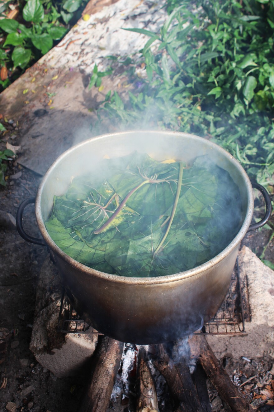 This steaming pot of oil down, with callaloo leaves on top, is ready to eat.